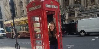 Madi Roswog stands inside a red phone booth in London.